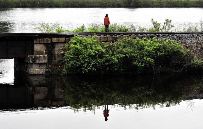ALONE: Paula Berry, daughter of missing driver Cora Marley, stands alone while looking for signs of her mother where Martin Stream and the Kennebec River meet in Hinckley on Wednesday.