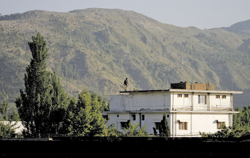 A Pakistan army soldier stands on top of the house where ial-Qaida leader Osama bin Laden lived in Abbottabad, Pakistan. Pakistan has convicted a doctor who helped the U.S. track down and kill bid Laden.
