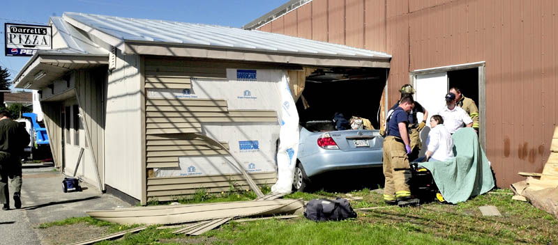 CRASH: Driver Sharon Roderick of Fairfield is treated on a gurney after being removed from her vehicle that crashed through a wall and into the Darrell's Pizza building in Waterville on Monday.