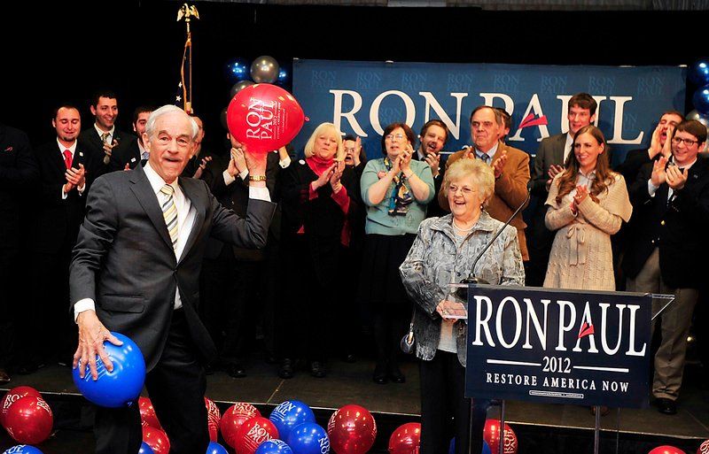 Texas Rep. Ron Paul, a Republican presidential candidate, tosses balloons to supporters in Portland, ME in February. Paul's supporters don't believe the presidential race is over, and are acting accordingly at GOP conventions.