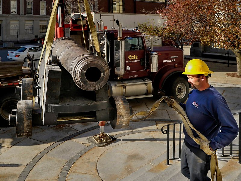 Steve Bosse, an employee of Cote Crane and Rigging, guides the historic cannon as a crane moves it from the steps of Portland City Hall to a truck for transport to the Maine Maritime Museum in Bath for the bicentennial exhibit of the War of 1812.