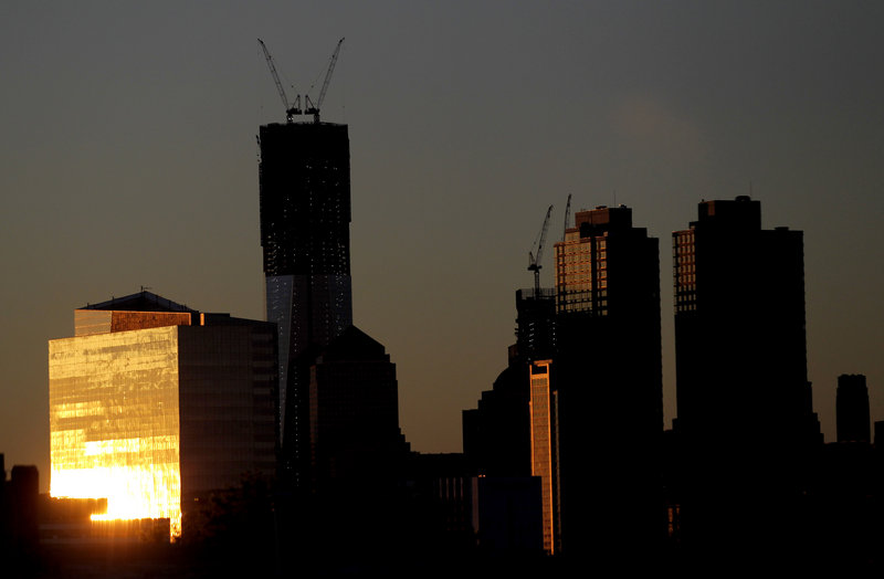 The sun reflects off buildings Monday, including One World Trade Center, center left, in New York. One World Trade Center replaces the twin towers destroyed on Sept. 11, 2001.