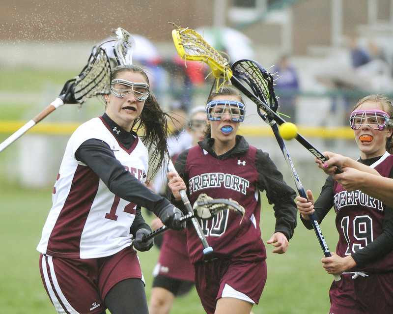 Paige Tuller of Greely takes a shot while being pursued by Freeport's Bethanie Knighton, center, and Emily Johnson during a lacrosse game Tuesday in Cumberland. Tuller scored on the shot, but Freeport rallied for a 12-11 victory.