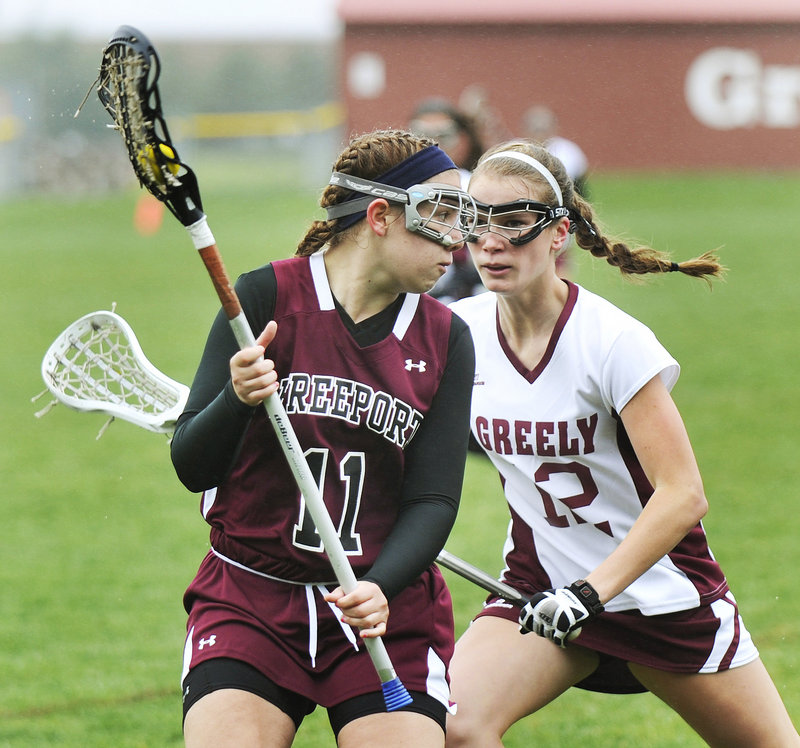 Kayla Thurlow of Freeport tries to get past Greely's Teal Otley after scooping up a ground ball. Freeport used a 7-0 run in the second half to improve to 2-2.