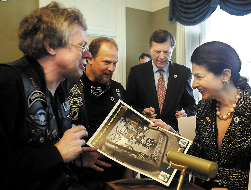 Sen. Olympia Snowe and her husband, former Gov. John McKernan, second from right, sign posters during the United Bikers of Maine annual tea at the Blaine House in Augusta.