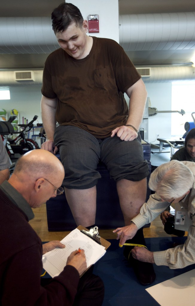Igor Vovkovinskiy of Rochester, Minn., the tallest man in the United States, has his feet measured by shoe technicians as part of a shoe fitting at Reebok headquarters in Canton, Mass., Thursday.