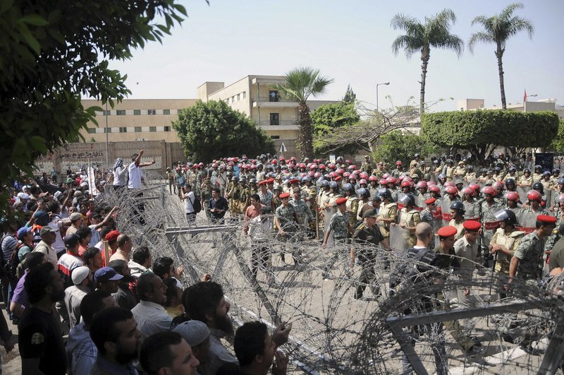 Protesters and security forces face off across a barbed wire barricade in Cairo Wednesday. After Wednesday's clashes, the military warned Thursday that deadly force was still an option.