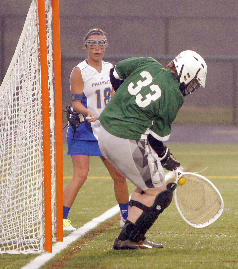Waynflete goalie Katherine Torrey blocks a shot as Falmouth's Vanessa Audet looks on. Torrey finished with 11 saves against a Falmouth team that was averaging more than 15 goals per game.