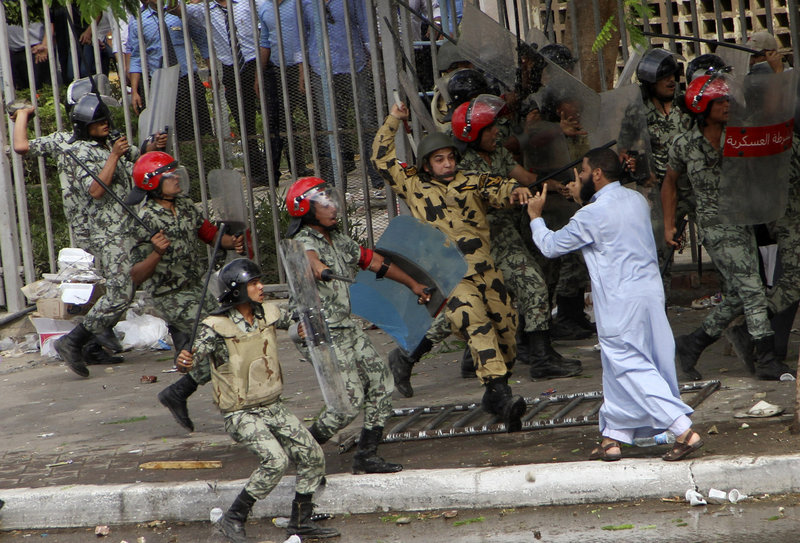 Egyptian soldiers raise their batons at a protester during clashes outside the Ministry of Defense in Cairo Friday. Fierce street battles raised fears of a new cycle of violence.