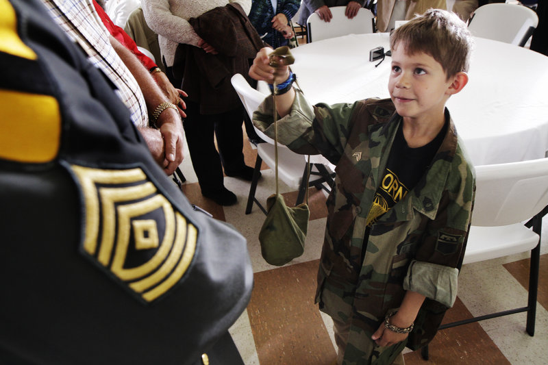 Jack McKibben, 7, of Cape Elizabeth acknowledges his grandfather, 1st Sgt. David Blouin, left, who received a silver star, like the one shown below, from the state for being wounded during the Vietnam War. A ceremony at the Maine Military Museum on Saturday paid tribute to dozens of service members and their families.