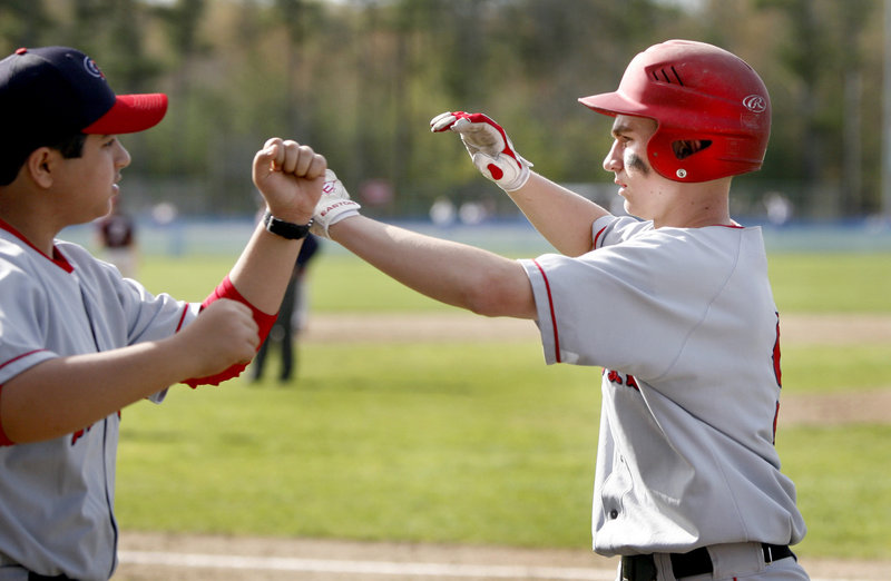 Justin McKenna of Gray-New Gloucester is congratulated Saturday after scoring the first run of the game in the third inning of a 5-0 victory against Freeport that sent the Falcons to their first loss. Gray-New Gloucester is 4-3.