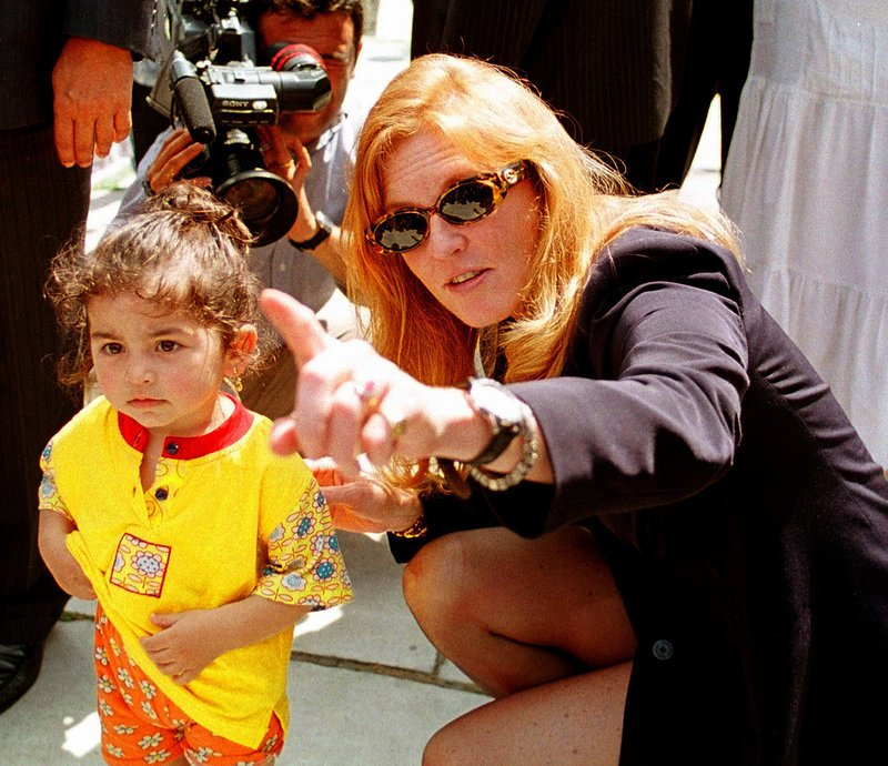 Sarah Ferguson kneels beside a Turkish child during a visit to Istanbul's Blue Mosque in 1998. She could serve up to 22 1/2 years in prison if convicted of taking part in the secret filming of two orphanages in Turkey.