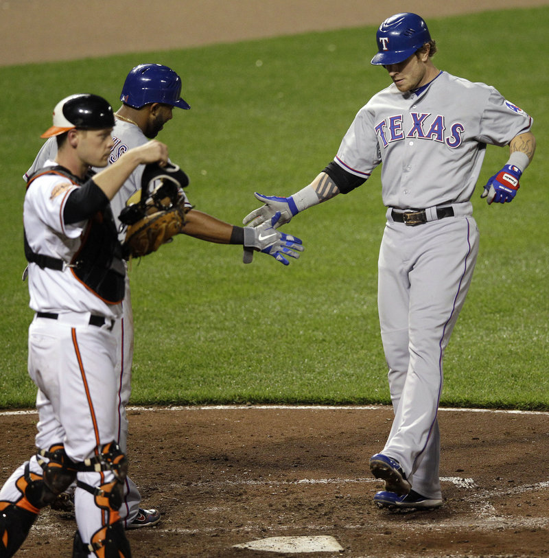 Josh Hamilton of the Rangers gets greeted at home after the third of his four home runs Tuesday night in Baltimore.