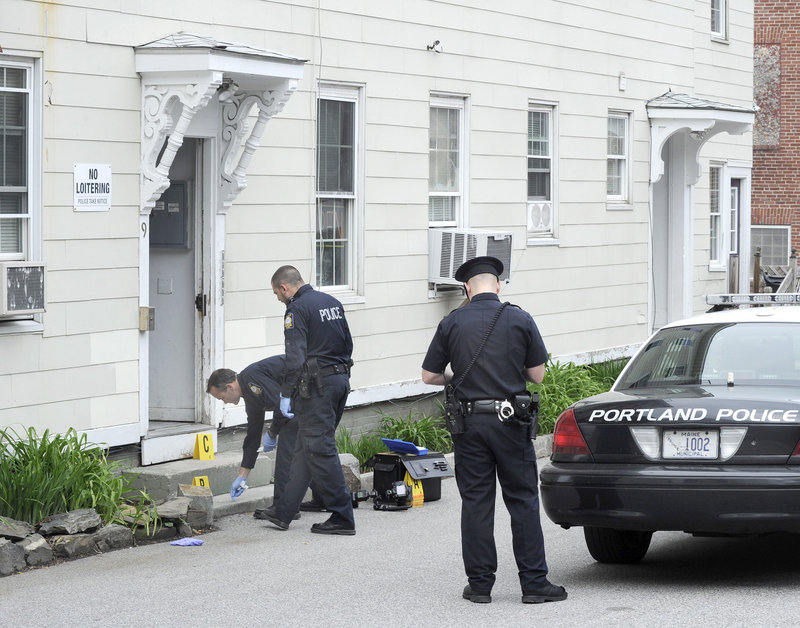 Portland police officers investigate the scene of a stabbing Wednesday outside 9 Cedar St. in Portland.
