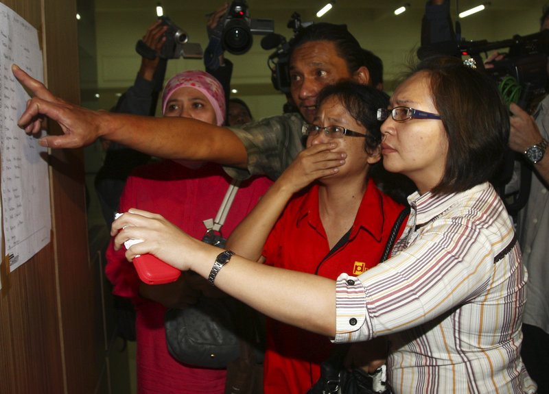 Relatives inspect the list of passengers on board a missing Russian plane at the airport in Jakarta, Indonesia, Wednesday.