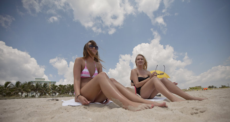 Morgan Weese, 23, left, and Brittany Locke, from Tempe, Ariz., sunbathe in Miami Beach, Fla., on Wednesday. Weese said she now knows the dangers of tanning too much.