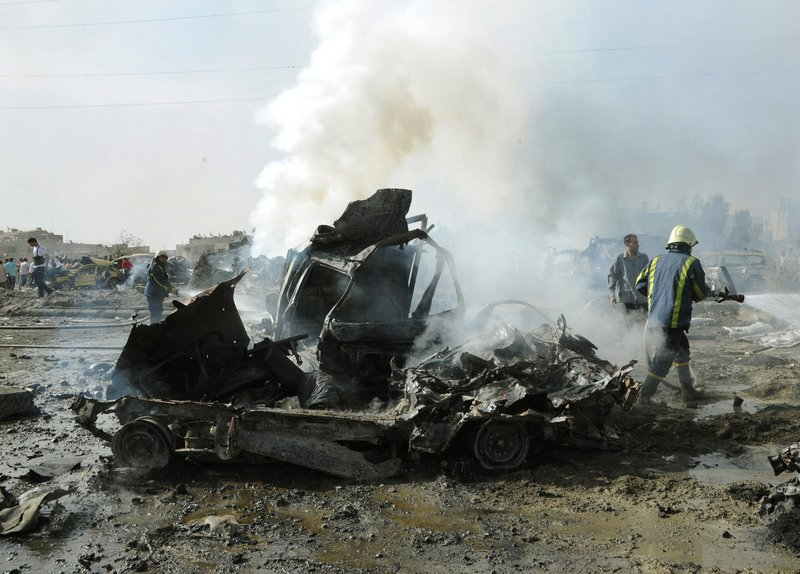 Syrian firefighters put out fires at one of dozens of cars destroyed by two bombs Thursday in Damascus. A military intelligence building was heavily damaged in the blasts.