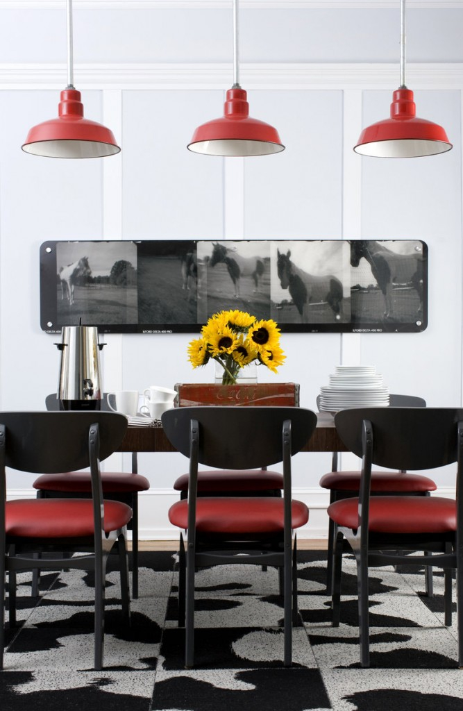 A dining room designed by Brian Patrick Flynn demonstrates how the designer balances space vertically by grounding a room with pendant lighting.