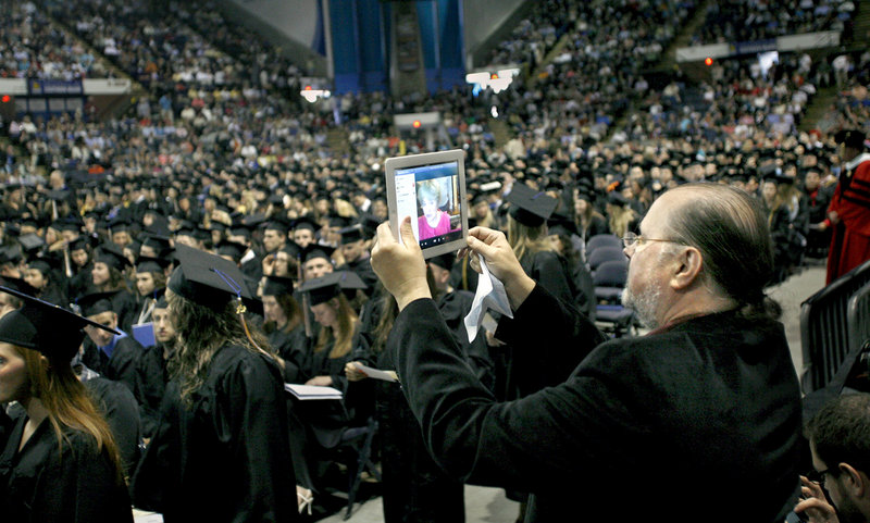 Jack Smith of Sanford holds up an iPad to Skype the graduation ceremonies to his daughter-in-law's parents living in Belarus during the USM commencement Saturday. Anastasiya Smith received her degree in psychology.