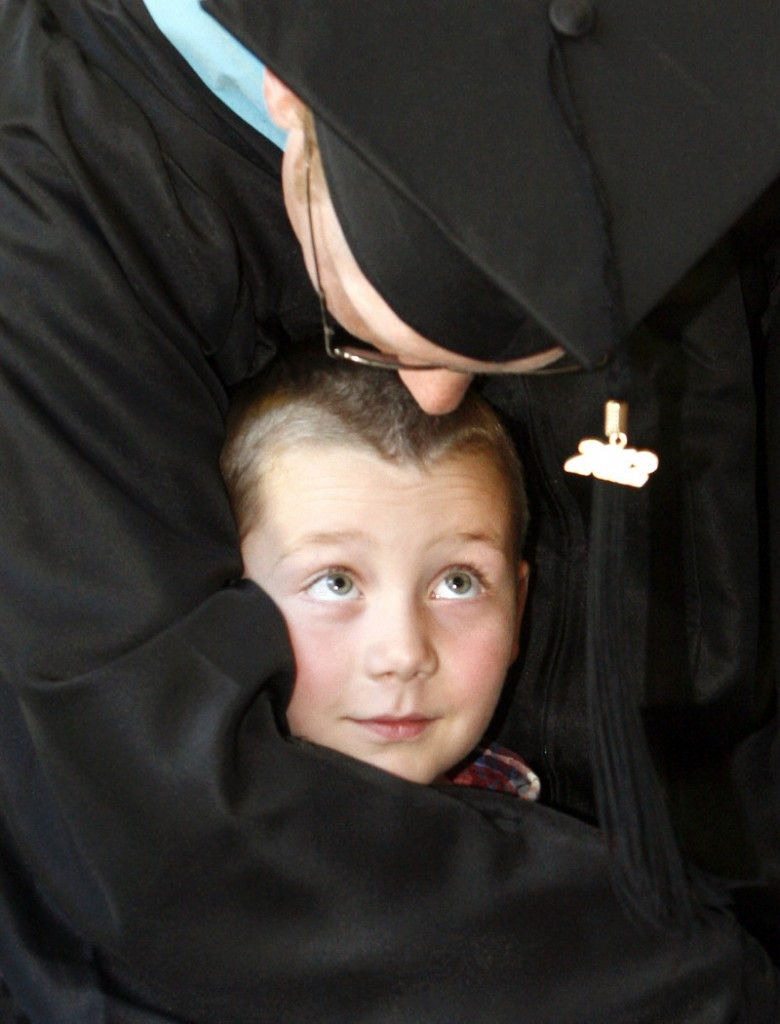 Seth Vincent of Auburn wraps his arms around his son Brady, 6, after receiving his master's degree in educational psychology during the USM commencement Saturday.