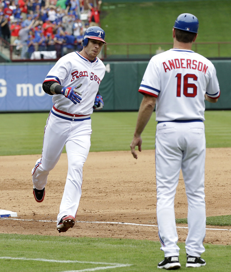 Josh Hamilton greets third-base coach Dave Anderson after Hamilton hit his ninth home run of the week during the Angels' 4-2 win over the Rangers on Saturday.