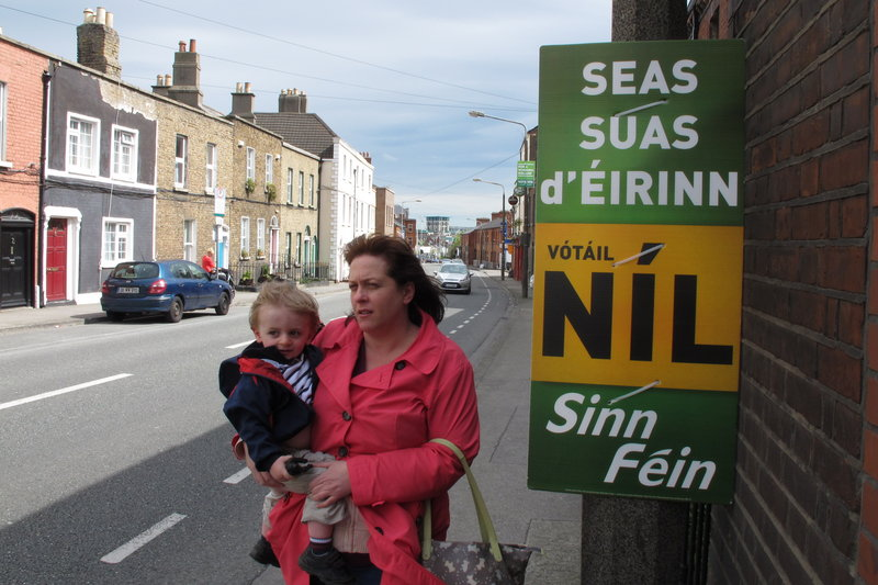 A mother and child walk past a poster urging a