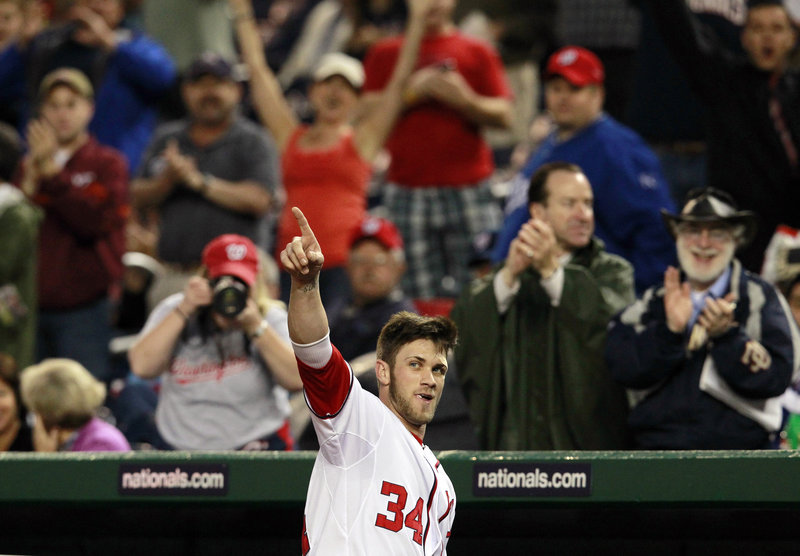 Bryce Harper of the Nationals salutes the crowd after hitting his first major league home run Monday night against the Padres in Washington. The Nationals won, 8-5.