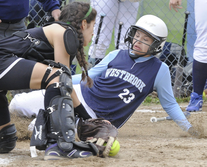 Nicole Nutter of Westbrook slides safely into the plate Tuesday as Marshwood catcher Gianna Riccardi fields the ball during Wesbrook's 7-6 victory at home.