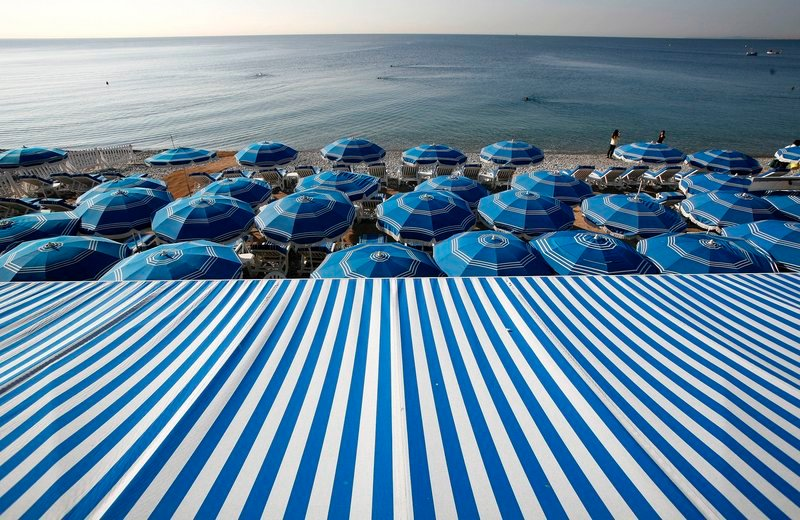 A sea of beach umbrellas provides shade from the sun along the beach in Nice, France.