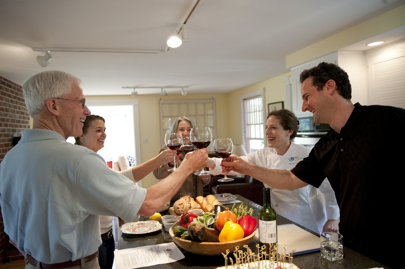 Michelle Goldman toasts students during a recent Mediterranean cooking class held in a Portland home. Goldman hosts more classes this week in Lincolnville and at SMCC.