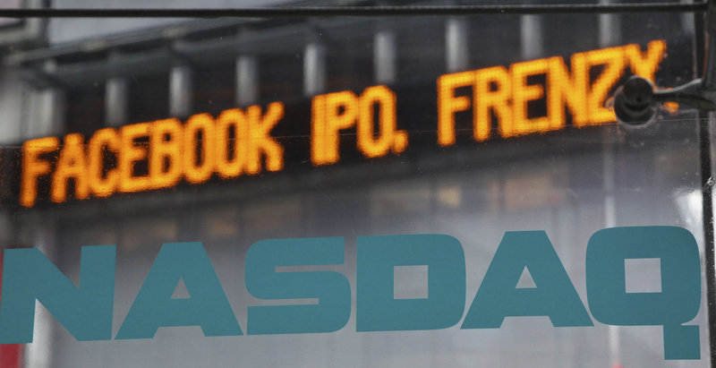"""News about the Facebook IPO passes on a billboard Tuesday outside of NASDAQ in Times Square, New York. With little hope of buying shares at the initial offering price, small investors face a """"euphoric"""" first-day price."""