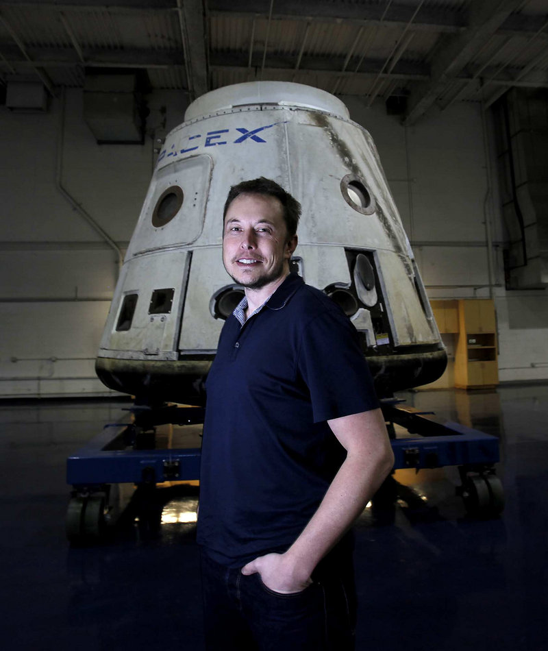 CEO Elon Musk stands with the SpaceX Dragon capsule at the company in Hawthorne, Calif. A Dragon scheduled to launch Saturday will carry cargo into orbit, and three days later dock with the International Space Station.
