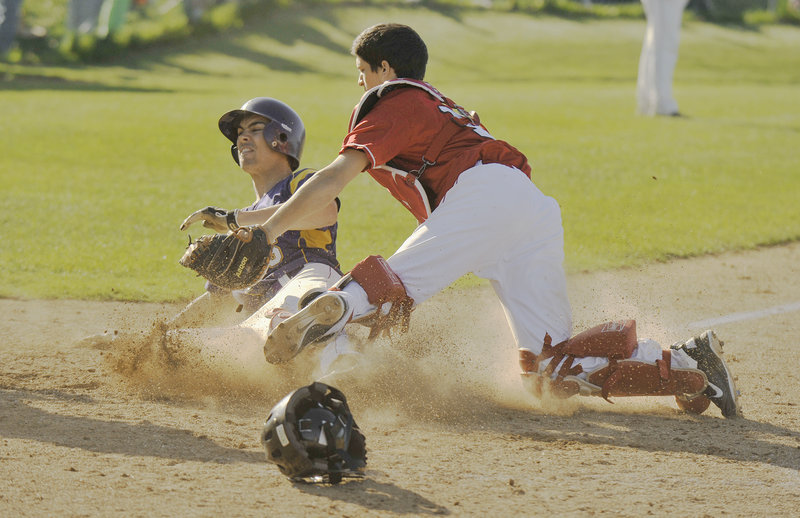 South Portland catcher Adam Helmke tags out Louie DiStasio of Cheverus in the sixth inning Thursday. The Stags had two runners thrown out at the plate in the inning but had built enough of a lead to defeat the Red Riots, 9-4.