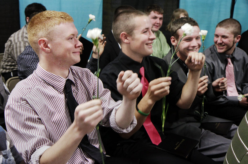 Portland Arts & Technology High School graduates Carl Ahlquist of Scarborough, Charlie Buxton of Windham and Nate Dobson of Falmouth sway to the music during the school's commencement ceremony on Friday.