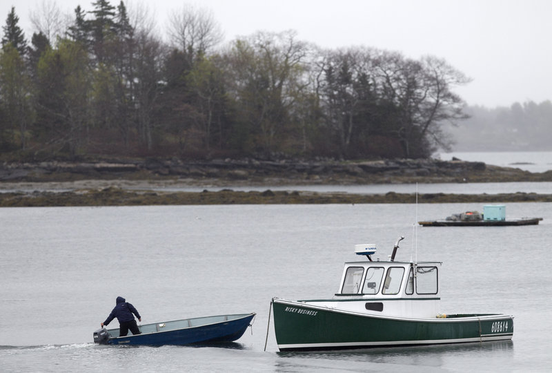 A fisherman motors his skiff out to a lobster boat. CO2 dissolves in seawater, producing acid that lessens the strength of small lobsters' shells and makes them more vulnerable to predators.