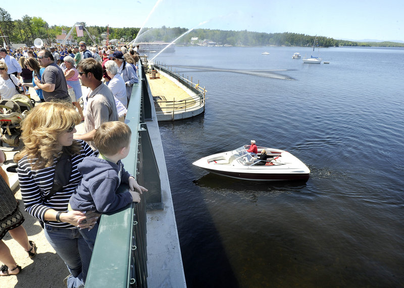 Julie Carlson of Naples holds her grandson, 3-year-old Jaiden Meehan, as they wait for state and local officials to celebrate the opening of the bridge between Long Lake and Brandy Pond on Friday. The entire project could be finished by this fall.