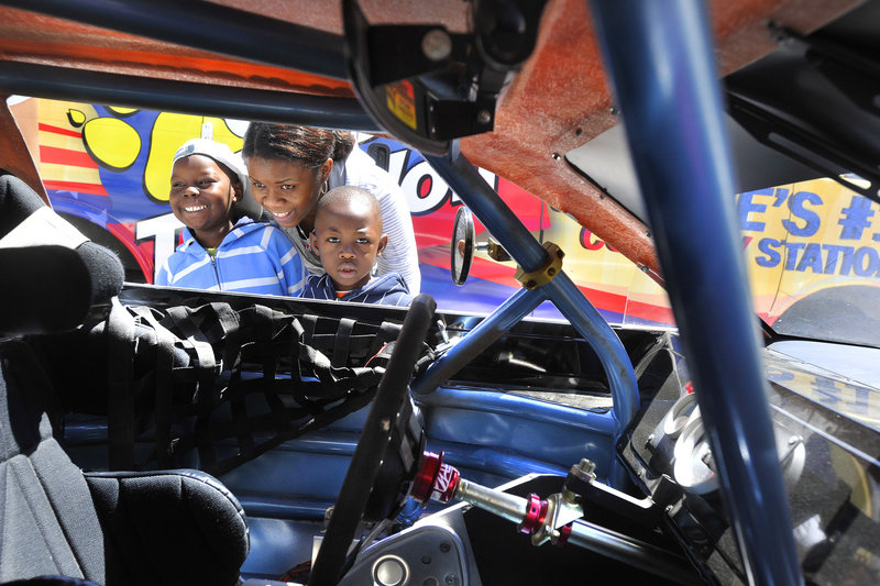 Evelyne Kanru of the Youth Outreach Family day-care program shows the interior of a race car to Noel, left, and Cedric. The cars in Monument Square in Portland on Friday were from Oxford Plains Speedway, which will be the site of an American Canadian Tour race Sunday.