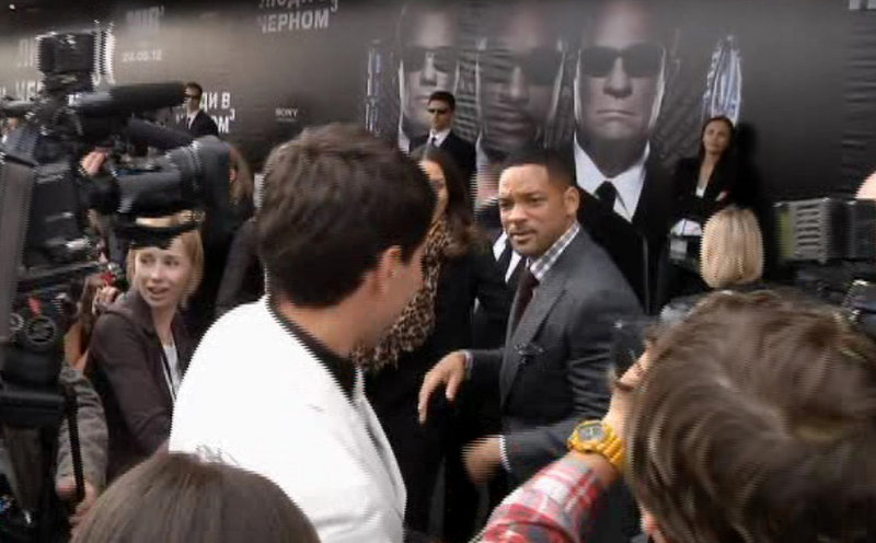 "Will Smith, center right, walks away from reporter Vitalii Sediuk, in white suit, after slapping him before the premiere of ""Men in Black III"" on Friday in Moscow."