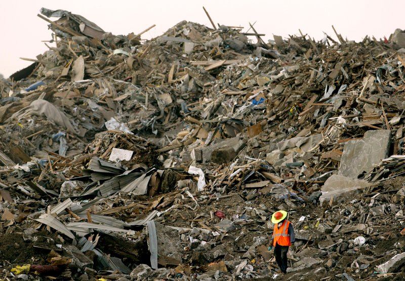 A worker walks amid a landfill in Galena, Kan., in 2011, where tornado debris had been hauled from nearby Joplin, Mo. The tornado was the costliest since 1950, at $2.8 billion.