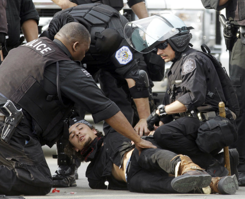 A protester is detained at a march and rally during the NATO summit in Chicago on Sunday. A group of demonstrators clashed with police outside the convention center.