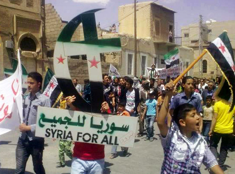 In this citizen journalism image, a protester against the regime of Syrian President Bashar Assad holds up a Cross and Crescent painted the colors of the Syrian revolutionary flag during a protest Friday in Yabroud, Syria. On Sunday, an anti-Assad cleric and his bodyguard were killed in Lebanon.