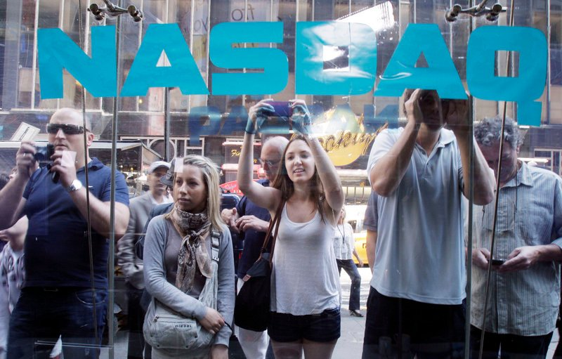Spectators watch through the windows at Nasdaq in New York as Facebook shares began trading on Friday. Enthusiasm for the stock has slipped after a record $104 billion valuation.