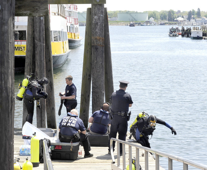 Portland police divers prepare to search the waters between the Maine State Pier and Maine Wharf for Nathan Bihlmaier, who disappeared in the Old Port early Sunday.