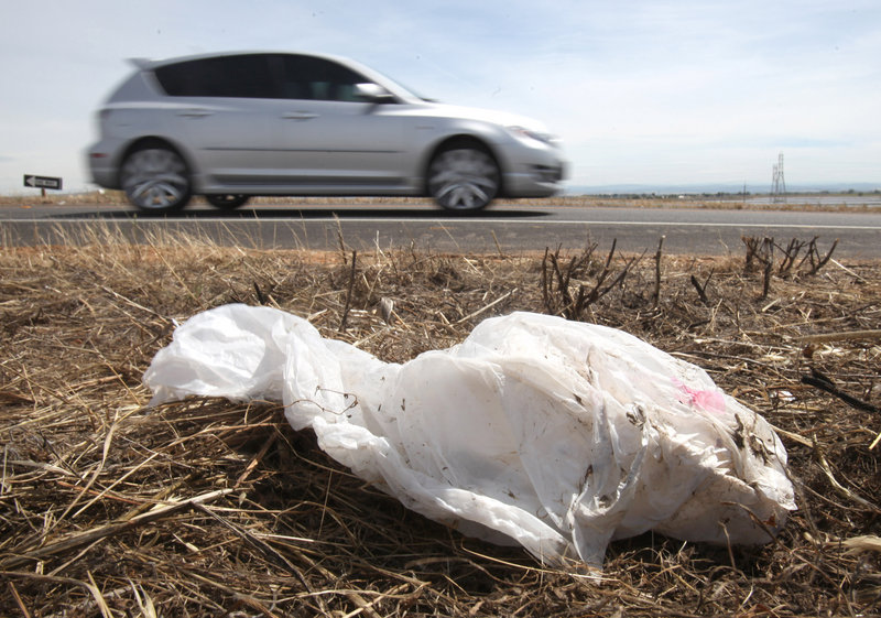 A car drives past a plastic bag on the ground near Olivehurst, Calif., in 2010.