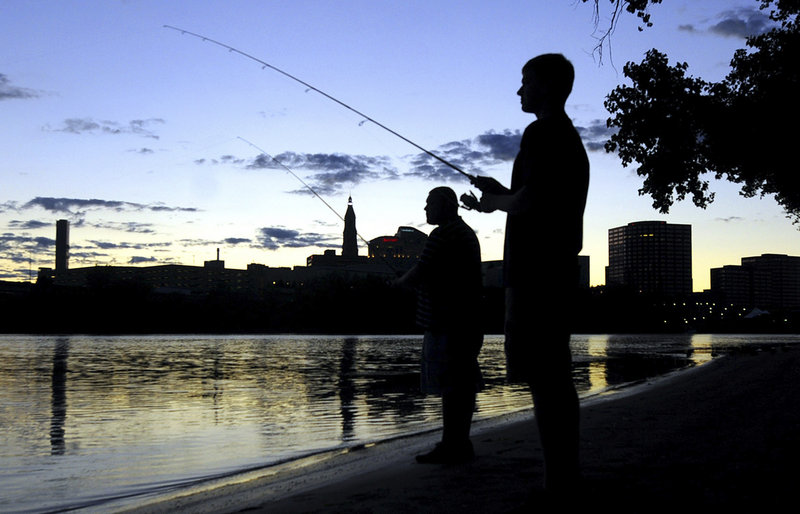 """Peter Murawski, foreground, and his cousin Joe Murawski fish on the banks of the Connecticut River at Great River Park in East Hartford, as the sun sets behind the Hartford skyline. Environmental awareness led to the river's """"rebirth."""""""