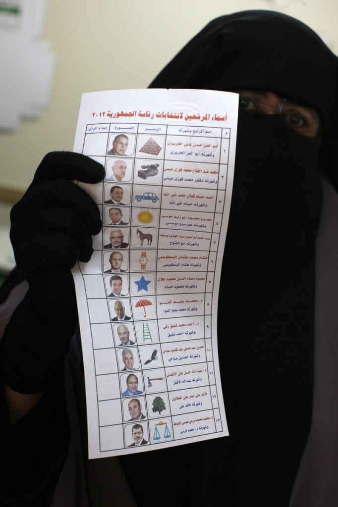 An Egyptian woman holds the ballot paper with names of the 13 presidential candidates at a polling station in Cairo on Thursday.