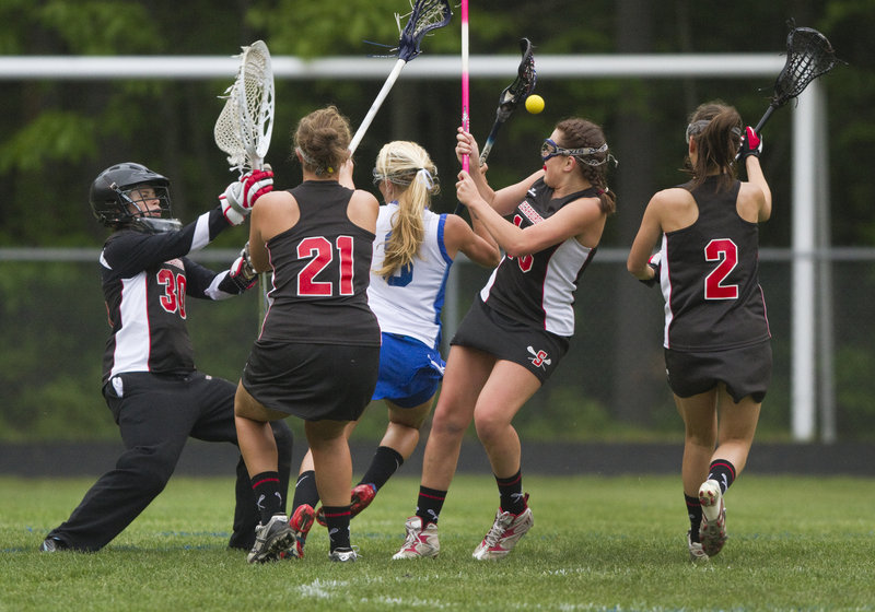 Rose Bryant of Kennebunk is surrounded by two Scarborough defenders, as well as goalie Meg Kirsh, who made eight saves.
