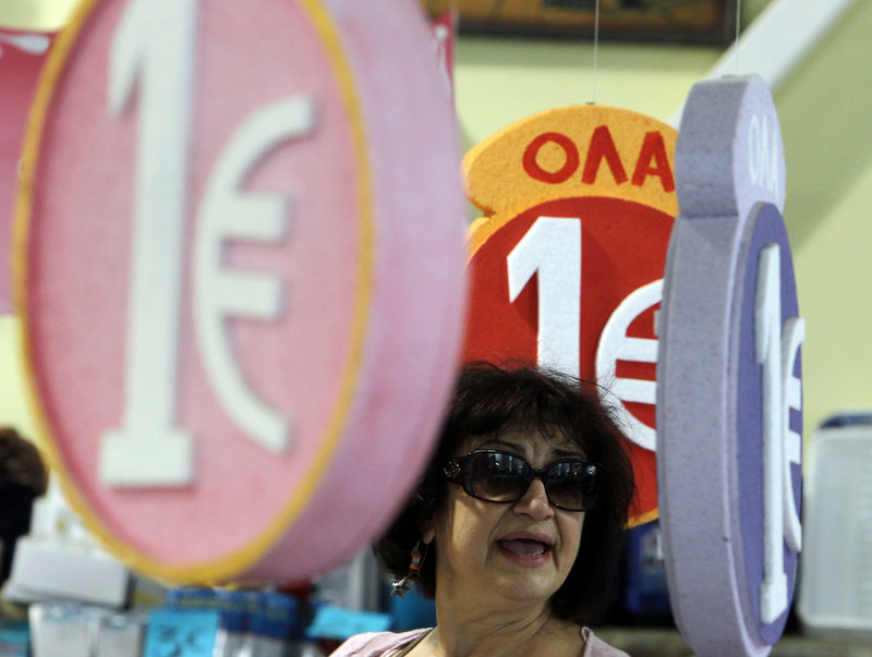 Signs advertising merchandise on sale for one euro are seen Friday in a discount shop in central Athens. Uncertainty over Greece's future in the eurozone has hammered markets ahead of June 17 general elections.