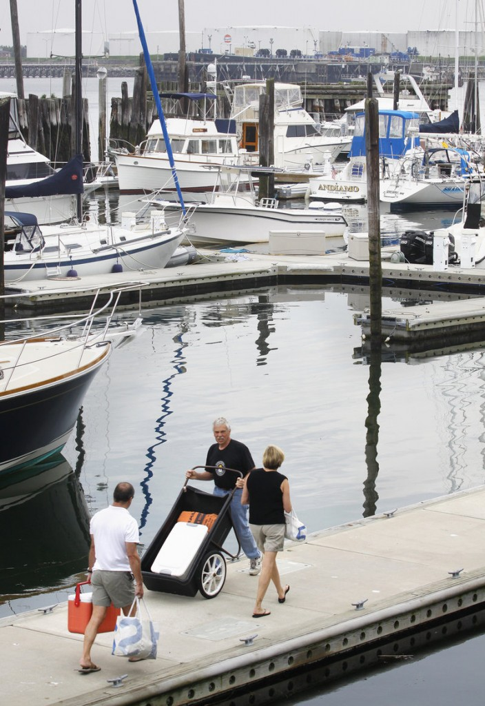 A worker passes a couple heading toward their vessel at DiMillo's marina in Portland on Saturday, where the U.S. Coast Guard Auxiliary offered free boater safety inspections.
