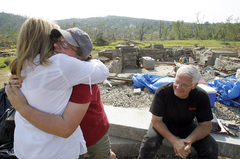 Diana Robbins, left, and Pia Rogers hug as Rogers' neighbor Dwight Meacham sits in front of Rogers' destroyed home last year after a tornado blew through Monson, Mass. The storm took a heavy toll, but it also brought people together to clear debris and weigh what to do next.